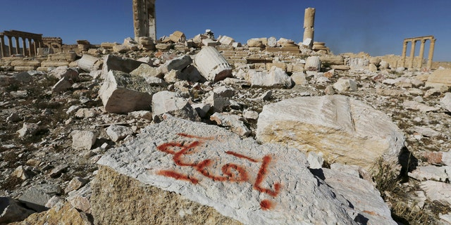 "File photo - Graffiti sprayed by Islamic State militants which reads ""We remain"" is seen on a stone at the Temple of Bel in the historic city of Palmyra, in Homs Governorate, Syria April 1, 2016."
