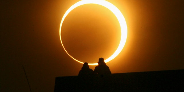 Two men sit on a bridge to watch an annular solar eclipse in Zhengzhou, Henan province, January 15, 2010. The longest, ring-like solar eclipse of the millennium started on Friday, with astronomers saying the Maldives was the best place to view the phenomenon that will not happen again for over 1,000 years. REUTERS/Donald Chan (CHINA - Tags: ENVIRONMENT SOCIETY) - RTR28W1C