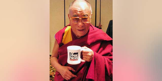 His Holiness the Dalai Lama poses with his FOX News mug after an interview.