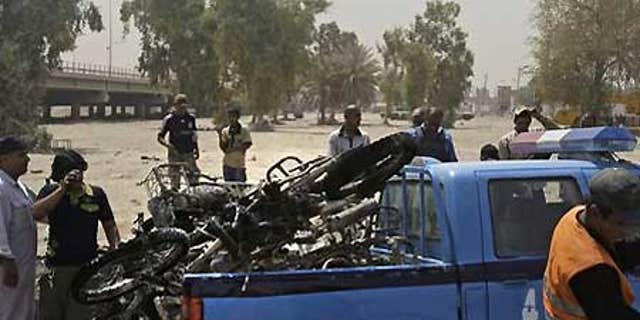 June 26: Iraqis load destroyed motorcycles in Baghdad, Iraq, after a booby-trapped motorcycle exploded in a crowded bazaar in Baghdad.