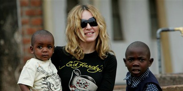 **  FILE  **** FILE ** Madonna holds David Banda in her arms, in this April 19, 2007, file photo at Consol Homes, a day care center that she is funding in the village of Masekese, Malawi. Officials say Madonna is to travel to Malawi to try to adopt a second child from the impoverished African country. An official at the Malawi welfare department said Thursday, March 26, 2009 that the pop star has filed adoption papers. (AP Photo/Karel Prinsloo, File)