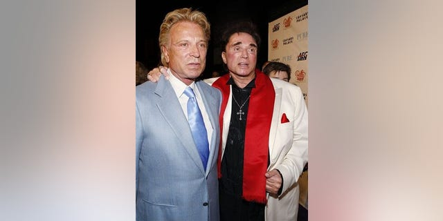 "** FILE ** In this Feb. 20, 2008 file photo, Siegfried Fischbacher, left, and Roy Horn arrive at a party following the premiere performance of Bette Midler's ""The Showgirl Must Go On"" at Caesar's Palace hotel and casino in Las Vegas. (AP Photo/Isaac Brekken, file)"