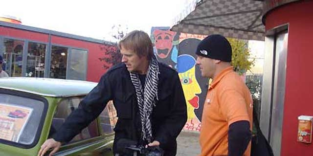 Fox News cameraman, Olaf Wiig, examines an old Trabi.