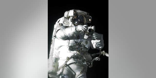 Atlantis shuttle astronaut Robert Satcher Jr. holds a camera during his mission's first spacewalk