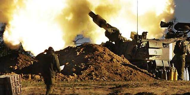 Jan. 6: Israeli Army soldiers take cover as a mobile artillery piece fires towards targets in the southern Gaza Strip.
