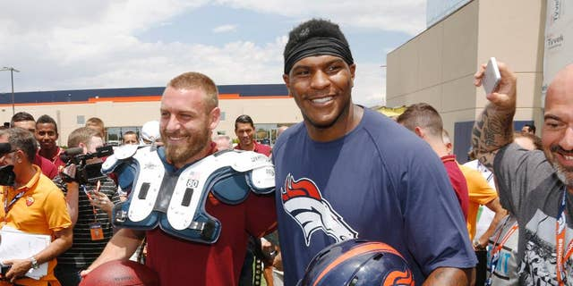 AS Roma player Daniele De Rossi, left, tries on the shoulder pads of Denver Broncos tight end Julius Thomas as members of the Italian soccer team meet Broncos players after the Broncos' NFL football training camp session in Englewood, Colo., on Friday, July 25, 2014. AS Roma is in Denver to face Manchester United on Saturday. (AP Photo)