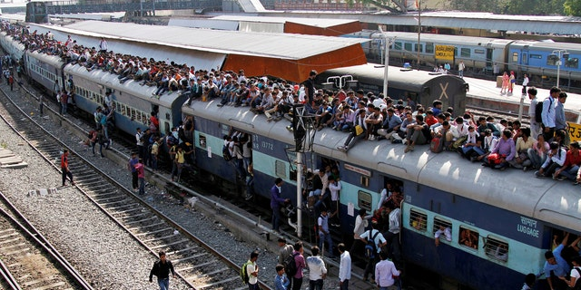 Passengers board an overcrowded train at a railway station in Ajmer, India.