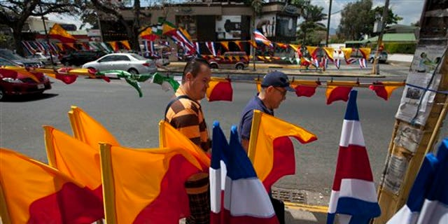CORRECTS NAME TO LUIS GUILLERMO SOLIS - Men walk next to Costa Rican flags and political party flags, in San Jose, Costa Rica, Saturday, April 5, 2014. Costa Rica will vote on the Sundays runoff presidential election between Luis Guillermo Solis, presidential candidate of Citizen's Action Party and ruling party candidate Johnny Araya. (AP Photo/Moises Castillo)