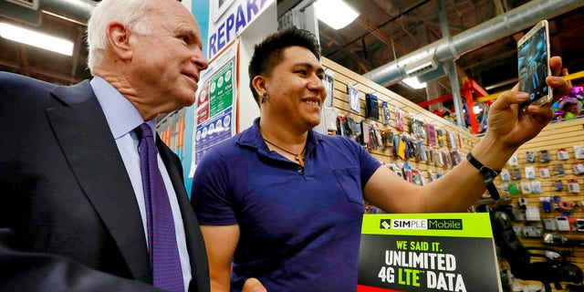 U.S. Sen. John McCain, R-Ariz., poses for a selfie with shop owner Aron Mercado at the El Mercado De Los Cielos mall prior to announcing the launch of  the âUnidos Con McCainâ Hispanic coalition, Thursday, Oct. 15, 2015, in Phoenix. McCain is trying to woo Hispanic voters to his re-election effort by putting together a coalition of Latino business leaders who back the Republican. (AP Photo/Matt York)