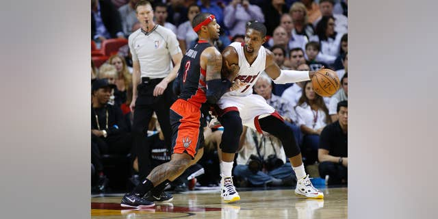 Toronto Raptors' James Johnson (3) defends against Miami Heat's Chris Bosh (1) as he attempts to drive to the basket during the second half of an NBA basketball game in Miami, Sunday, Nov 2, 2014. The Heat defeated the Raptors 107-102. (AP Photo/Joel Auerbach)