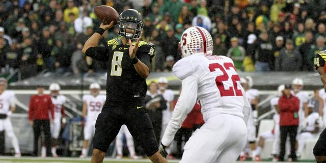 Oregon quarterback Marcus Mariota (8) looks to throw towards the end zone during the first quarter against Stanford in an NCAA college football game in Eugene, Ore., Saturday, Nov. 1, 2014. (AP Photo/Ryan Kang)