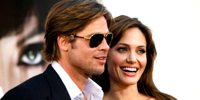 """Angelina Jolie and actor Brad Pitt pose at the premiere of """"Salt"""" in Hollywood, California July 19, 2010. (Reuters)"""