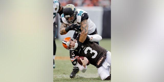 Cleveland Browns quarterback Brandon Weeden (3) is tackled by Jacksonville Jaguars defensive end Jason Babin (58) during the third quarter of an NFL football game on Sunday, Dec. 1, 2013, in Cleveland. (AP Photo/Tony Dejak)