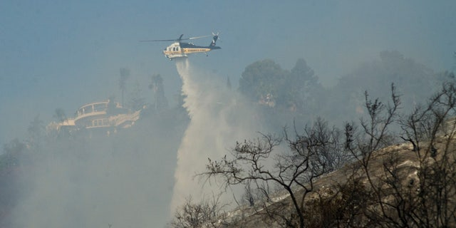A helicopter drops water on hotspots left by the Skirball fire near the Bel Air neighborhood on the west side of Los Angeles, California, U.S., December 6, 2017.