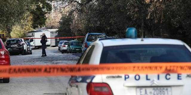 A policeman secures a street where police conduct an investigation at a suburb of Athens, Thursday, Jan. 5, 2017. Greek police say they have recaptured a convicted far-left militant wanted for more than four years after she absconded during her trial on domestic terrorism charges.