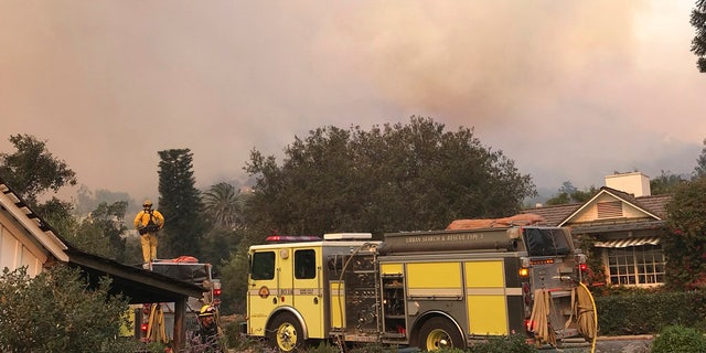 In this photo provided by the Santa Barbara County Fire Department,fire engines provide structure protection at the historic San Ysidro Ranch in Montecito, Calif., Saturday, Dec. 16, 2017.