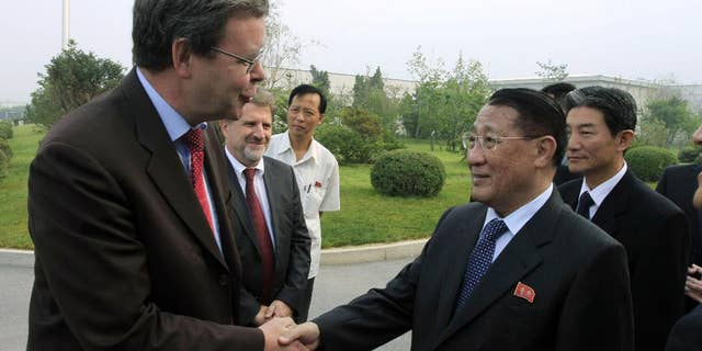 FILE - In this Sept. 6, 2014 file photo, North Korea's Kang Sok Ju, right, a member of the Political Bureau of the Central Committee of the Workers' Party of Korea (WPK) and secretary of the WPK, shakes hands with German Ambassador to North Korea Thomas Schaefer as he leaves Pyongyang Airport in Pyongyang, North Korea to visit Germany, Belgium, Switzerland, Italy and Mongolia. Kang, a top North Korean diplomat who negotiated a short-lived 1994 deal with the United States to freeze its nuclear programs in exchange for international aid, has died of cancer, the country's state media said Saturday, May 21, 2016. (AP Photo/Kim Kwang Hyon, File)