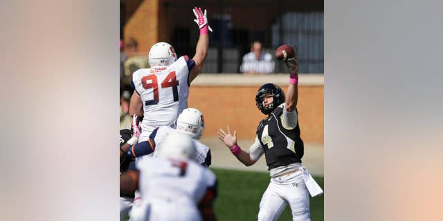 Wake Forest's Tyler Cameron (4) tries to throw a pass over Syracuse's Robert Welsh (94) during the second half of an NCAA college football game in Winston-Salem, N.C., Saturday, Oct. 18, 2014. Syracuse won 30-7. (AP Photo/Chuck Burton)