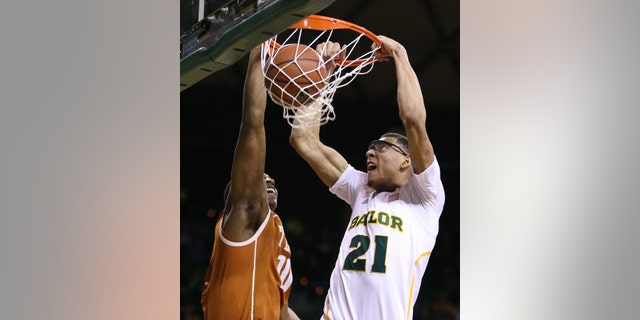 Baylor's Isaiah Austin (21) scores over Texas' Jonathan Holmes during the second half of a NCAA college basketball game, Saturday, Jan. 5, 2013, in Waco, Texas. Baylor won in overtime 86-79. (AP Photo/Waco Tribune Herald, Rod Aydelotte)