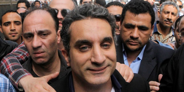 FILE - In this Sunday, March 31, 2013 file photo, a bodyguard secures popular Egyptian television satirist Bassem Youssef, who has come to be known as Egypt's Jon Stewart, as he enters Egypt's state prosecutors office to face accusations of insulting Islam and the country's Islamist leader in Cairo, Egypt. Youssef's show is scheduled to air Friday night, April 5, 2013, for the first time since he appeared in court last Sunday.(AP Photo/Amr Nabil, File)