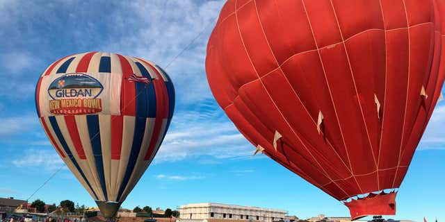 Two hot air balloons inflate at Vista Grande Elementary School in Rio Rancho, N.M. on Friday, Sept. 30, 2016, as part of the Albuquerque Aloft program that lifts balloons on school grounds as part of the 45th Albuquerque International Balloon Fiesta.