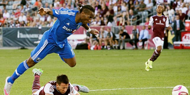 Oct 10, 2015; Commerce City, CO, USA; Montreal Impact forward Didier Drogba (11) leaps over a diving Colorado Rapids defender Sean St. Ledger (24) in the second half at Dick's Sporting Goods Park. The Impact defeated the Rapids 1-0. Mandatory Credit: Isaiah J. Downing-USA TODAY Sports
