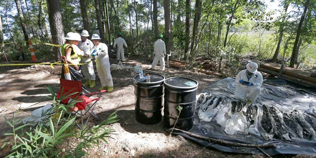 Contractors collecting and inspect soil samples taken at a Superfund cleanup site in Navassa, N.C., in 2015.