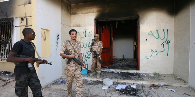File: Sept. 14, 2012: Libyan military guards check one of the burnt out buildings at the U.S. Consulate in Benghazi, Libya, during a visit by Libyan President Mohammed el-Megarif to express sympathy for the death of American ambassador to Libya Chris Stevens and his colleagues in the Sept. 11, 2012 attack.