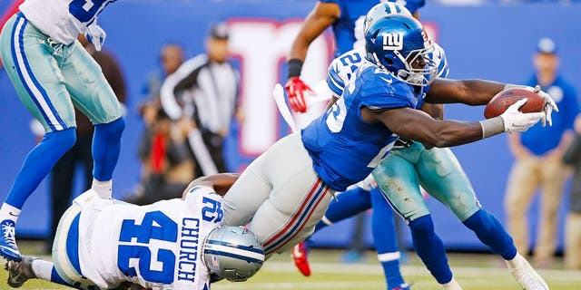 New York Giants running back Orleans Darkwa (26) dives past Dallas Cowboys' Barry Church (42) for a touchdown as Byron Jones (31) chases them during the first half of an NFL football game, Sunday, Oct. 25, 2015, in East Rutherford, N.J. (AP Photo/Kathy Willens)