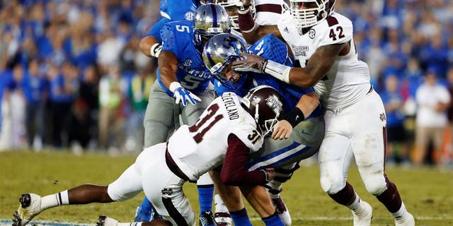Oct 25, 2014; Lexington, KY, USA; Mississippi State Bulldogs defensive back Tolando Cleveland (31) and linebacker Beniquez Brown (42) tackle Kentucky Wildcats quarterback Patrick Towles (14) in the second half at Commonwealth Stadium. Mississippi State defeated Kentucky 45-31. Mandatory Credit: Mark Zerof-USA TODAY Sports