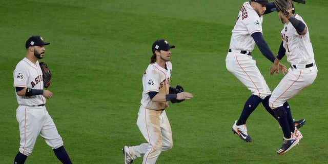 Houston Astros' Carlos Correa and George Springer celebrate after Game 3 of baseball's World Series against the Los Angeles Dodgers Friday, Oct. 27, 2017, in Houston.