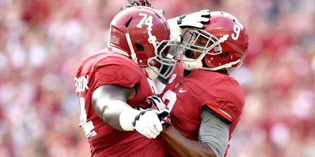 Sep 13, 2014; Tuscaloosa, AL, USA; Alabama Crimson Tide offensive linesman Cam Robinson (74) leaps up to celebrate wide receiver Amari Cooper (9) touchdown against the Southern Miss Golden Eagles during the first quarter at Bryant-Denny Stadium. Mandatory Credit: John David Mercer-USA TODAY Sports