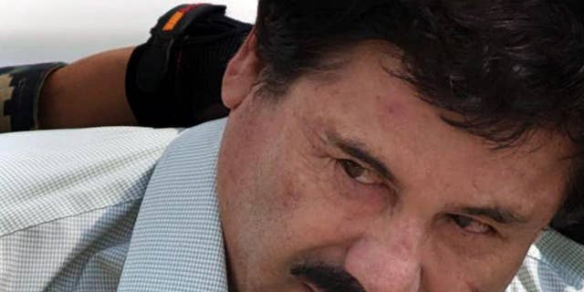 """FILE - In this Feb. 22, 2014, file photo, Joaquin """"El Chapo"""" Guzman is escorted to a helicopter by Mexican navy marines in Mexico City, Mexico. The normally bucolic, vacationer-laden Mexican state at the tip of Baja peninsula is now the scene of dozens of killings in what authorities call a power struggle resulting from the February arrest of international drug lord Joaquin """"El Chapo"""" Guzman. (AP Photo/Eduardo Verdugo, File)"""