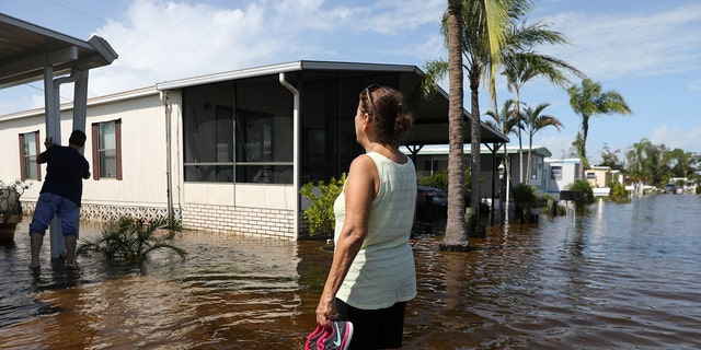 Marie Powell surveys damage to her property at a mobile home park after Hurricane Irma in Naples, Florida, U.S. September 11, 2017 REUTERS/Stephen Yang - RC118E108E70