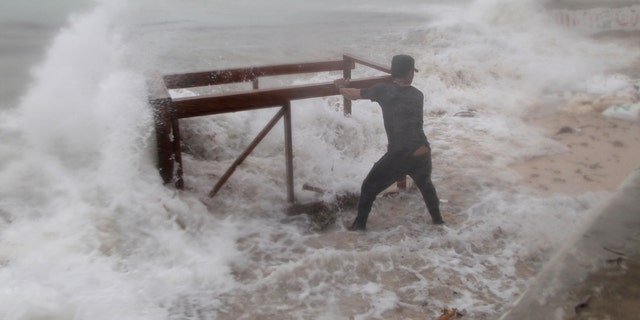 A man tries to salvage a table belonging to his restaurant before the arrival of Hurricane Maria in Punta Cana, Dominican Republic, September 20, 2017.