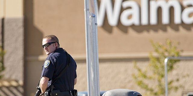 Oct. 29: Reno police officers search through trash cans in the parking lot during a standoff following a shooting at a Reno Walmart.