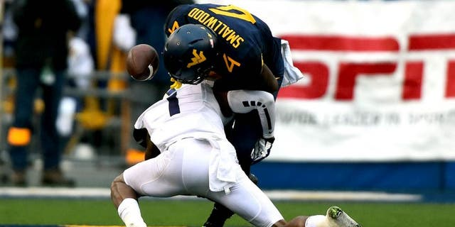 Nov 1, 2014; Morgantown, WV, USA; TCU Horned Frogs safety Chris Hackett (1) forces West Virginia Mountaineers running back Wendell Smallwood (4) to fumble during the second quarter at Milan Puskar Stadium. Mandatory Credit: Tommy Gilligan-USA TODAY Sports