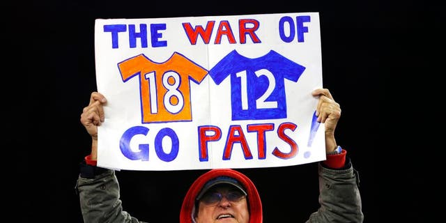 Nov 2, 2014; Foxborough, MA, USA; A fan holds up a sign about New England Patriots quarterback Tom Brady and Denver Broncos quarterback Peyton Manning during the fourth quarter of New England's 43-21 win at Gillette Stadium. Mandatory Credit: Winslow Townson-USA TODAY Sports