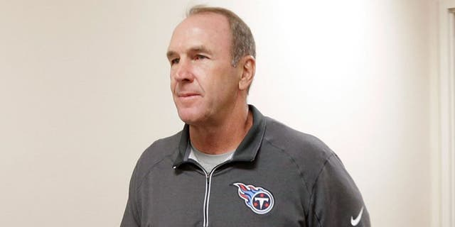 The Tennessee Titans assistant head coach/tight ends coach Mike Mularkey, left, walks to a news conference after it was announced that he has been named the interim head coach after the team fired head coach Ken Whisenhunt Tuesday, Nov. 3, 2015, in Nashville, Tenn. (AP Photo/Mark Humphrey)