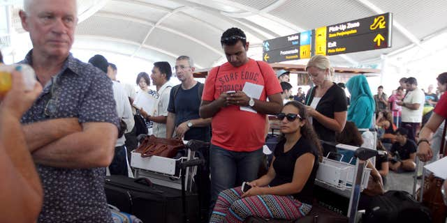 Nov. 4, 2015: Passengers wait to check the status of their flights with airline desk at Ngurah Rai International Airport in Bali, Indonesia.