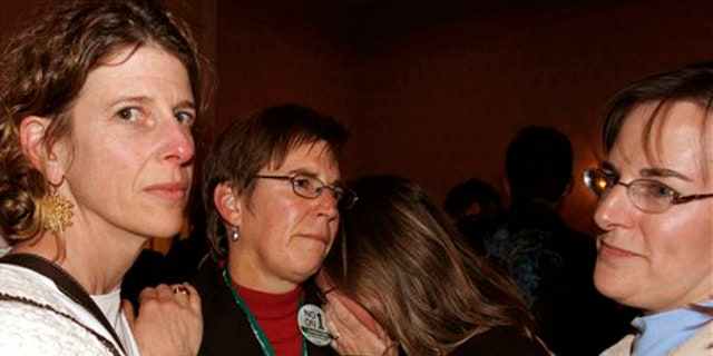 Friends console one another after learning about the unofficial defeat on Question 1 at election night headquarters in Portland, Maine, early Wednesday morning, Nov. 4, 2009 (AP)
