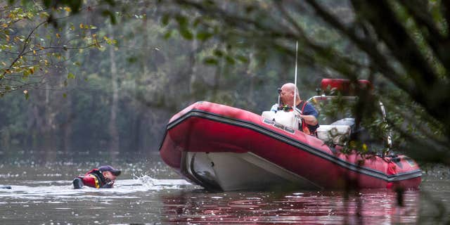 Nov. 4, 2015: Carl Hall, a Rescue Diver with Horry County Fire and Rescue swims back to the boat to join boat operator John Hall while searching a creek where a a 5-month-old girl is believed to be lost in Socastee Swamp waters after the mother said she put the baby in brown, swirling waters.