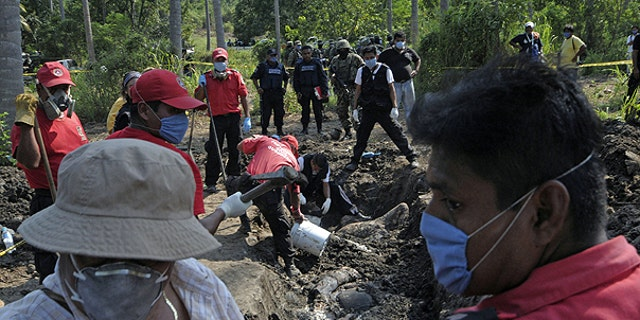 Nov. 3: Civil protection and forensic workers recover a body which was buried at a field in the town of Tuncingo, southern Mexico.