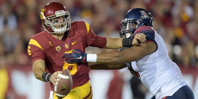 Nov 7, 2015; Los Angeles, CA, USA; Southern California Trojans quarterback Cody Kessler (6) is pressured by Arizona Wildcats defensive end Reggie Gilbert (8) at Los Angeles Memorial Coliseum. Mandatory Credit: Kirby Lee-USA TODAY Sports