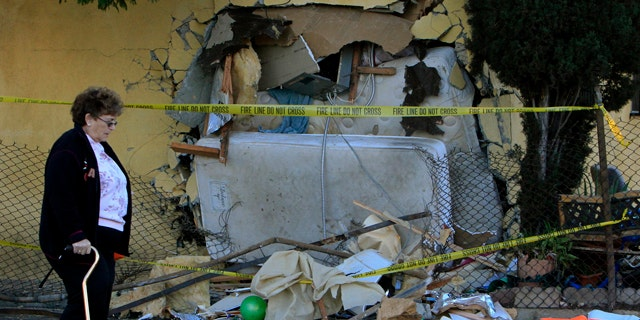 Nov. 1: A woman walks by a house that a pick up truck was driven into in Los Angeles.
