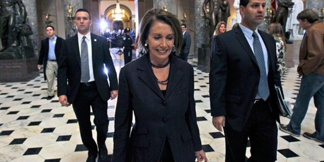 Nov. 10: House Speaker Nancy Pelosi walks past the set up for a news conference for House Speaker-in-waiting John Boehner.