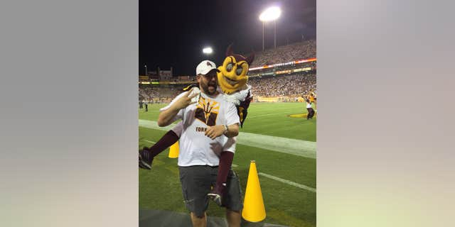 Sept. 18, 2015L This photo courtesy of David Schapira shows ASU's mascot Sparky jumping on David Schapira at a Arizona State University football game in Tempe, Ariz.