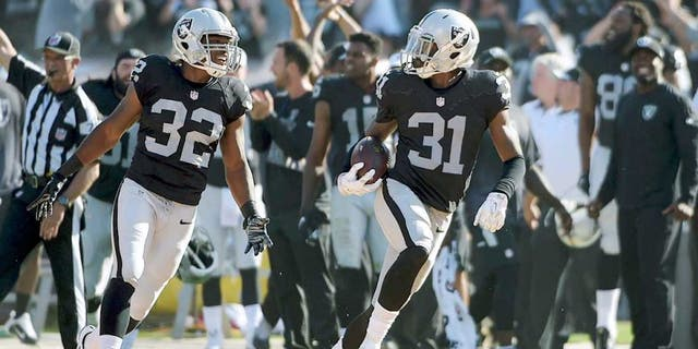Sep 20, 2015; Oakland, CA, USA; Oakland Raiders cornerback Neiko Thorpe (31) celebrates with safety Keenan Lambert (32) after intercepting a pass in the final minute against the Baltimore Ravens as at O.co Coliseum. The Raiders defeated the Ravens 37-33. Mandatory Credit: Kirby Lee-USA TODAY Sports