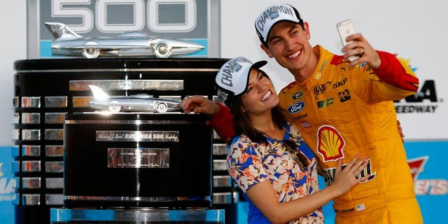 DAYTONA BEACH, FL - FEBRUARY 22: Joey Logano, driver of the #22 Shell Pennzoil Ford, and wife Brittany take a selfie in Victory Lane with The Harley J. Earl Trophy after winning the NASCAR Sprint Cup Series 57th Annual Daytona 500 at Daytona International Speedway on February 22, 2015 in Daytona Beach, Florida. (Photo by Jerry Markland/Getty Images)