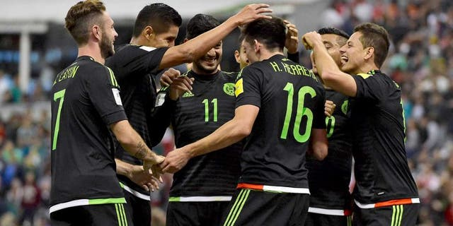 Mexico's Hector Herrera (16) celebrates with teammated after scoring against El Salvador during their Russia 2018 FIFA World Cup South American Qualifiers football match, in Mexico City on November 13, 2015. AFP PHOTO / ALFREDO ESTRELLA (Photo credit should read ALFREDO ESTRELLA/AFP/Getty Images)